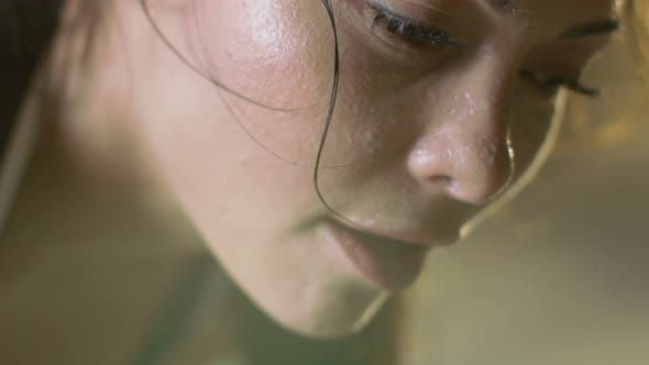 Close-up Shot of a Beautiful Athletic Woman Wipes Sweat from Her Forehead with a Hand