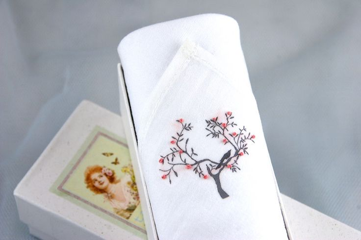 A delicate image of a tree is hand printed on this cotton handkerchief with blossom hand embroidered in tiny little knots.