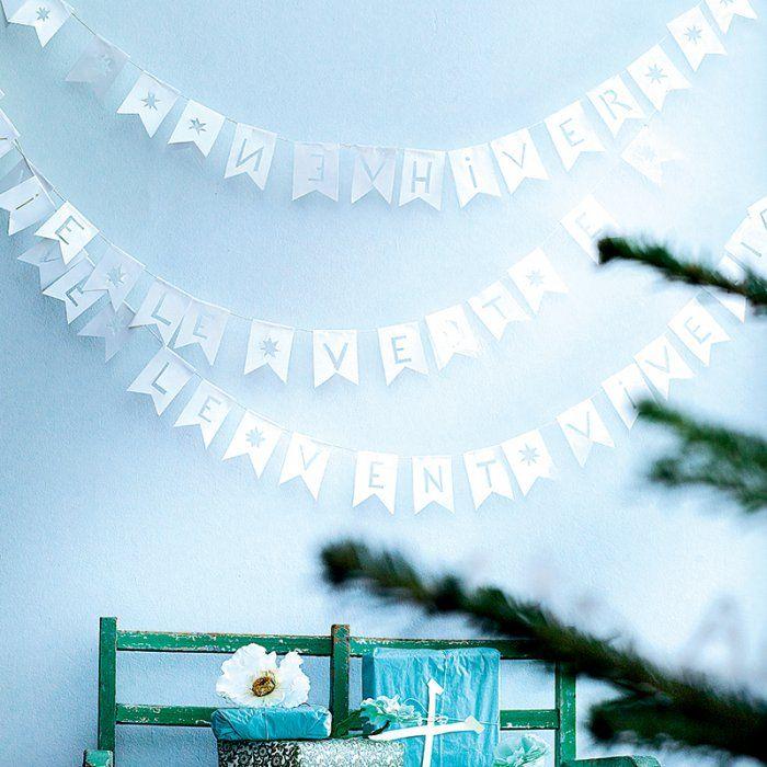 Des guirlandes de drapeaux blancs en papier ornés de lettres