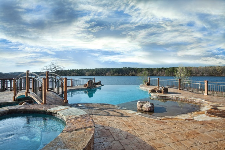 This amazing backyard features an automated freeform vanishing-edge infinity pool with a five-person hot tub, flagstone-lined beach entry, Pebble Tech pool finish, three waterfalls, and a graceful bridge. Elite Pools by Scott, Little Rock, Arkansas