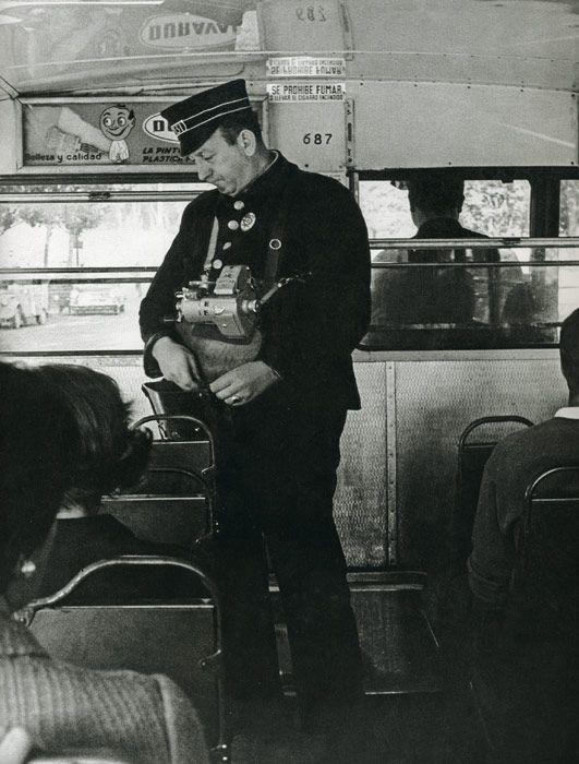 1967. Con rígida uniformidad, gorra incluida, un cobrador desempeña su trabajo a bordo de un autobús (con el volante a la derecha)