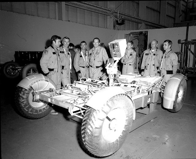 November 1971, (from left to right) Astronauts John Young, Eugene Cernan, Charles Duke, Fred Haise, Anthony England, Charles Fullerton, and Donald Peterson await deployment tests of the Lunar Roving Vehicle (LRV) qualification test unit in Building 4649 at the Marshall Space Flight Center (MSFC).
