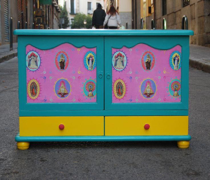 """Pequeño aparador de estilo clásico que hemos transformado tapizando las puertas con una tela de nuestra primera colección, en concreto: """"Virgen rosa"""", y pintando el mueble en un verde turquesa y amarillo.  La transformación ha sido total, convirtiendo un clásico en un elemento """"kitsch"""" de lo más pintoresco.  De esta mesilla sólo tenemos una unidad, ya que es única.  Si te gusta este trabajo, podemos personalizar un mueble tuyo o hacerte uno por encargo."""