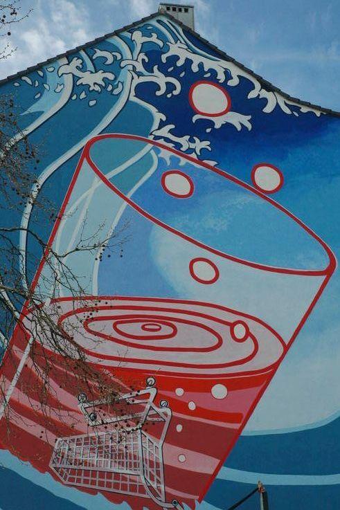 """Über Morsestraße und Bilker Allee geht es weiter zur Bachstraße. Hier kann man seit 2011 ein Werk von Klaus Klinger und seinem polnischen Kollegen Ivo Nikic an einer Häuserwand bewundern. Der in einem Trinkglas versenkte Einkaufswagen darf als Konsumkritik verstanden werden – schließlich liegt das Haus direkt gegenüber des Einkaufszentrums """"Düsseldorf Bilk Arcaden"""", das viele bis heute für genauso überflüssig halten wie den sprichwörtlichen Kropf."""