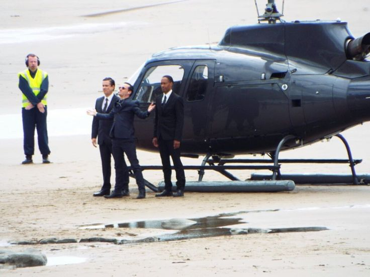 SHERLOCK (BBC) ~ Behind the scenes during Season 4 filming on July 5, 2016: Andrew Scott as Moriarty, center, exits a helicopter. [Link to Geekfeed article.]
