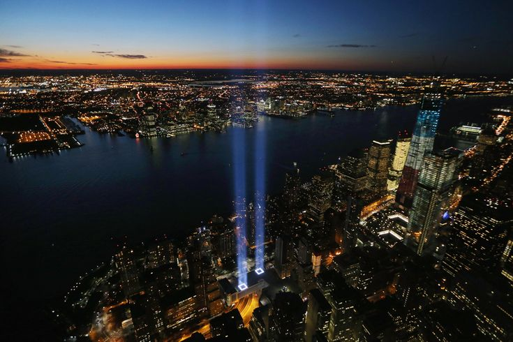 he Tribute in Light shines as One World Trade Center (right) rises under construction on the 11th anniversary of the terrorist attacks on lower Manhattan at the World Trade Center on Sept. 11 in New York. (Mario Tama/Getty Images) #