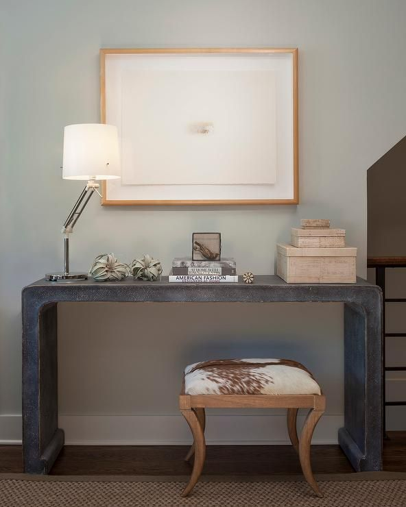 Chic foyer features a white and brown cowhide stool tucked for Furniture for curved wall in foyer