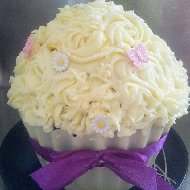 Chocolate giant cupcake cake with cream cheese frosting topped with Daisy's and butterflies.  Cupcake casing is made from white chocolate.   To order your giant cupcake or for any other party queries follow the link below  www.facebook.com/totaleventplanning