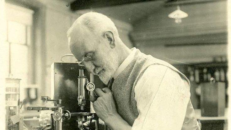 G.B. Bidder sitz an einem Tisch und schaut durch ein Mikroskop.