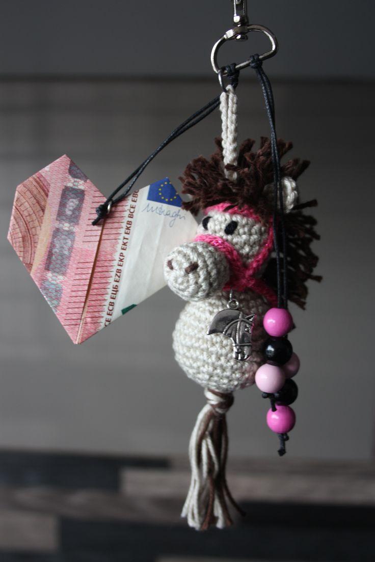 Een sleutelhanger gemaakt van een gehaakt paardje. Aan het paardje wat bedels en kraaltjes gehangen en een gevouwen hartje van geld. Leuk verjaardagscadeau voor een paardenmeisje.