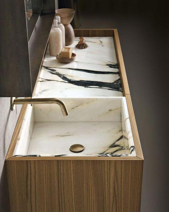 lavabo de mármol pulido que representa elegancia al tener el blanco, negro y unos toques de dorado.