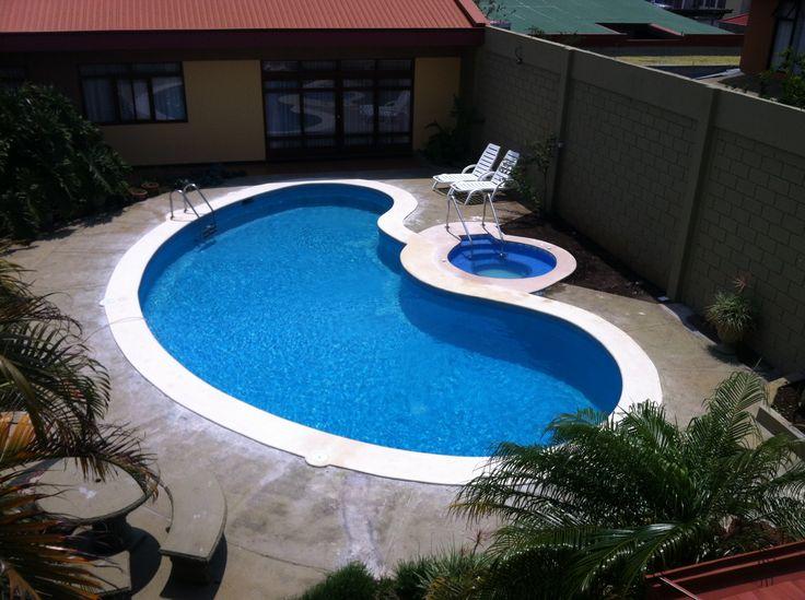 Piscina en forma de frijo con spa incorporado for Fotos de piscinas modernas en puerto rico