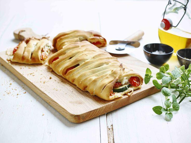 Gevlochten pizzabrood met vulling van salami, zongedroogde tomaten, groene asperges en mozzarella.