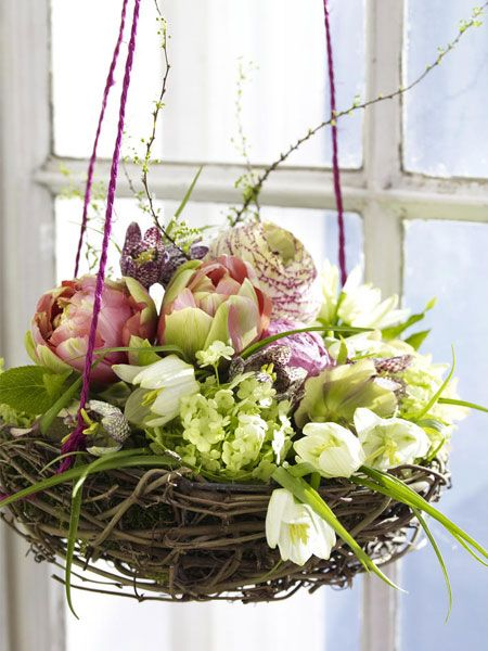 Nest of spring flowers in a hanging wicker basket