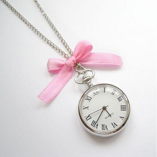 Originální funkční hodinky ve stříbrné barvě s římskými číšlicemi, zavěšené na řetízku a doplněné růžovou mašlí. Průměr hodinek je 3 cm, délka řetízku 80 cm....