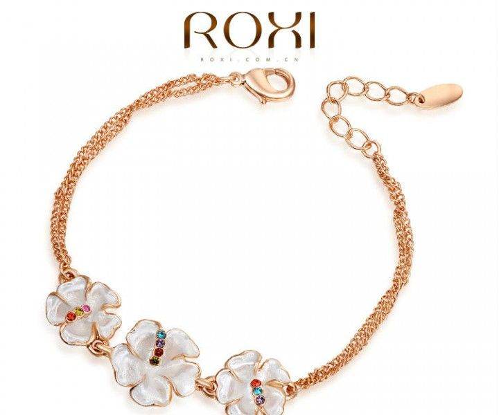 Goud vergulde armband met witte bloemen. De bloemen zijn versierd met echte Oostenrijkse kristallen.