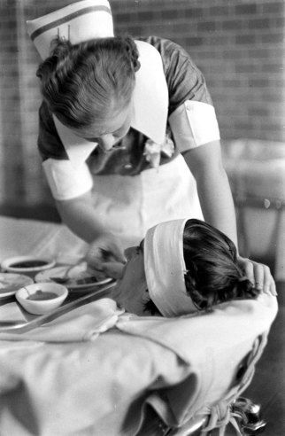 Pilgrim State Hospital, Brentwood, NY, 1938. Feeding a mental patient who is strapped into a continous-flow tub.