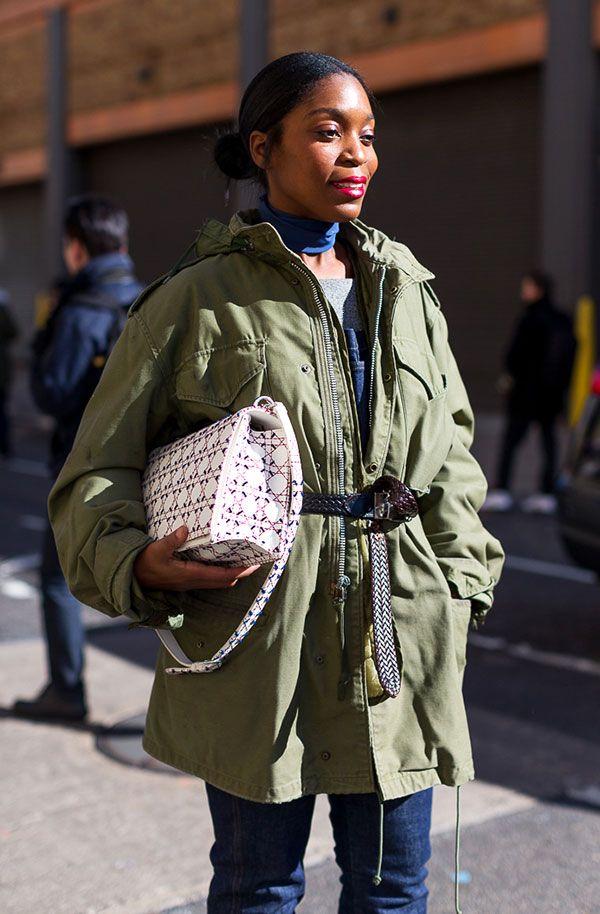 Look com calça jeans, parka verde, usando cinto como truque de stylling amarrado sobre o casaco.