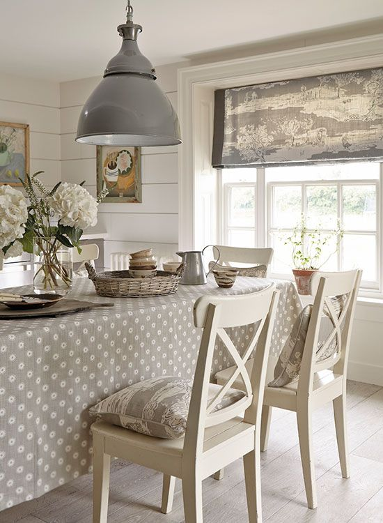 Adorable dining room with cream chairs, great light fixture, and a polka dot tablecloth
