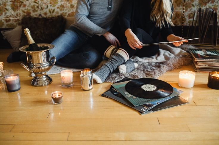 couple sitting on floor with candles and looking at records
