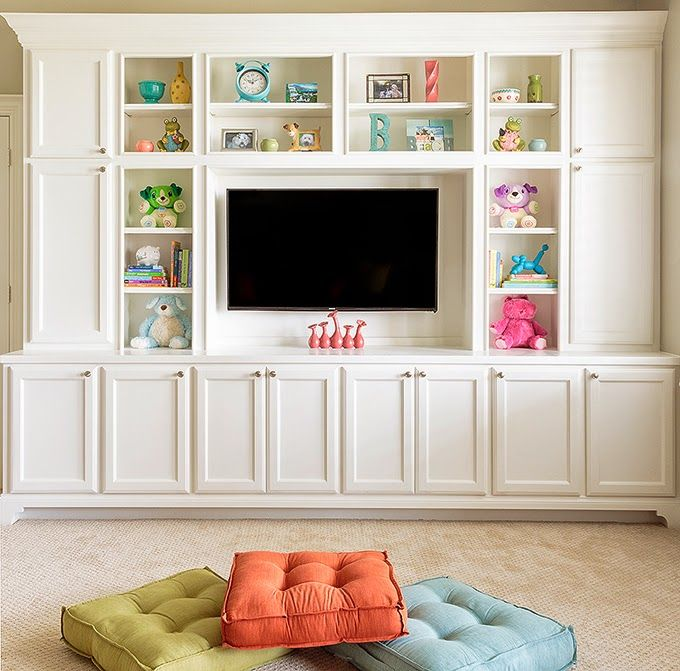 Built-in cabinetry with open shelving and TV. Kid-friendly basement toy storage.