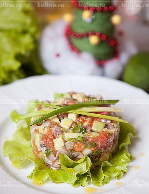 На блюдо положить листья салата, поставить кольцо, выложить тартар, кольцо снять. Украсить перьями зеленого лука и подать к столу.