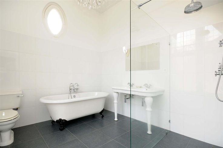 Traditionele badkamer met een vrijstaand bad op pootjes.