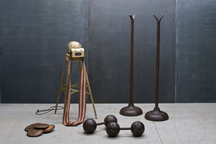 """USA, c.1920s. Early Century Gym Equipment, Cast Iron Bar Bell Stands Mfg. by York. Raised Lettering in Base, """"YORK"""" and """"BAR BELL"""" Good Vintage Condition, Showing Wear, Oxidation and Piting to Metal Surfaces.    Dia: 13 x H: 53 in."""