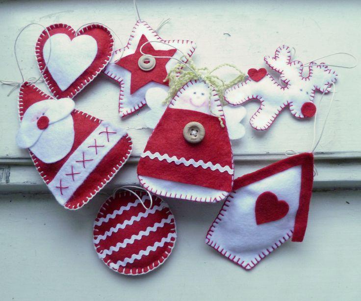 Vánoční ozdoby sada 7 kusů Ručně šité vánoční ozdoby na stromeček či jako milý dáreček jsou vyrobeny z červeného a bílého filcu a vyplněny vatou. Rozměr ozdob je: srdíčko 7,5 cm, baňka 7,5 cm, hvězda 8 cm, santa 12 cm, sob 9,5 cm, domeček 11,5 cm, andílek 10,5. Zavěšeno na smetanové voskované šňůrce.