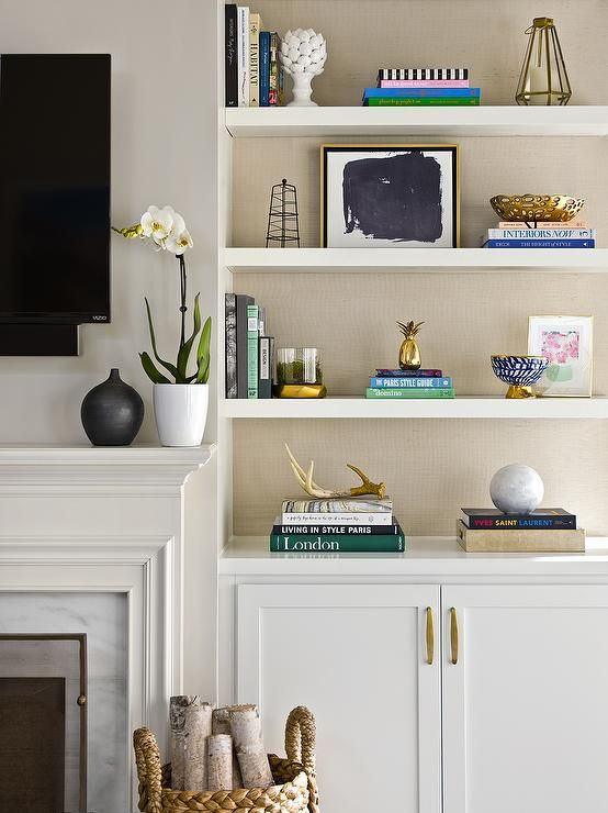 Beautifully decorated transitional living room is equipped built-in styled white  shelves accented with tan