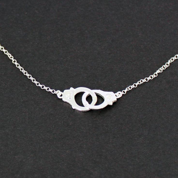 Collar realizado en plata de ley de 925 milésimas. Esposas unidas con un corazón en la cerradura.Incluye cadena de 35 centímetros con un alargador de 5 centímetros adicionales.