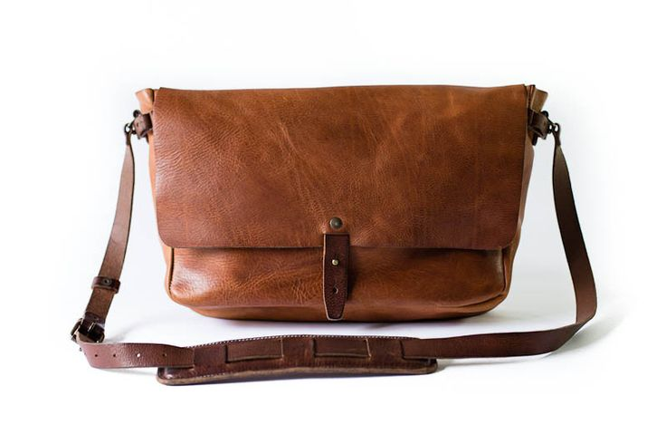 """The Vintage Messenger Bag from Whipping Post  The Vintage Messenger is a tribute to antique postal bags, albeit an updated, leaner version that includes a suede-lined laptop compartment. The bag is constructed of 100% vegetable tanned leather and includes an adjustable padded strap, key lanyard and back newspaper pouch.  18.5"""" x 11.5"""" x 4"""" Pictured with a 13"""" Macbook Pro"""