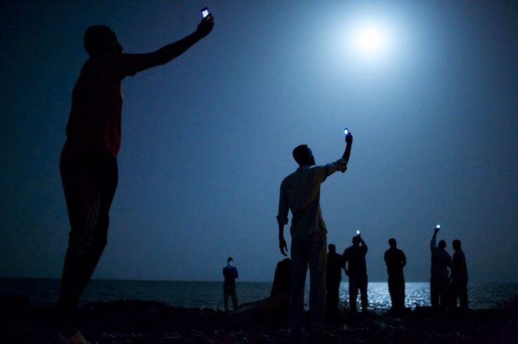 African migrants on the shore of Djibouti City at night raise their phones in an attempt to catch an inexpensive signal from neighboring Somalia—a tenuous link to relatives abroad. Djibouti is a common stop-off point for migrants in transit from such countries as Somalia, Ethiopia and Eritrea, seeking a better life in Europe and the Middle East.
