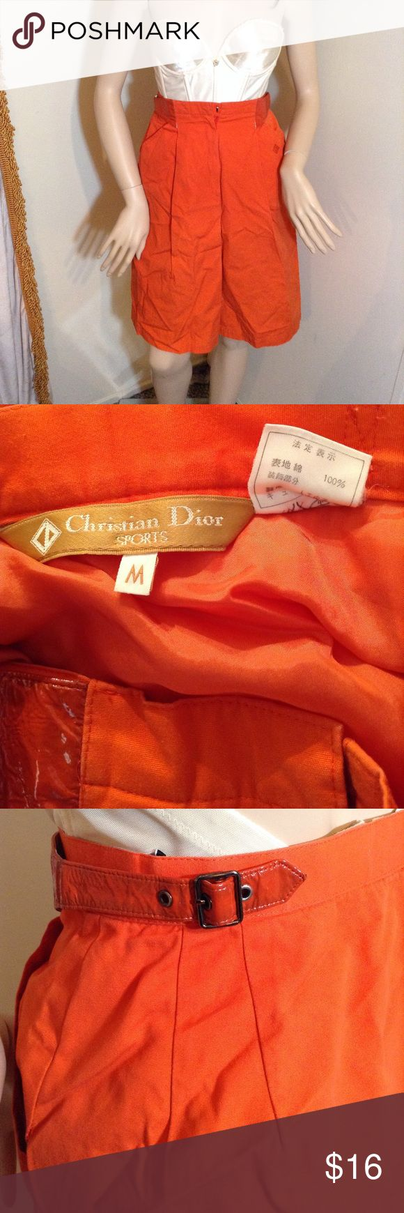 "Vintage Christian Dior Sports Orange Skirt Vintage Christian Dior Sports orange skirt. Two front pockets. Skirt is lined in orange fabric. Patent side buckles at the waist. The underside of both buckles is peeling from age. See picture closeup. The patent buckle material has discoloration and is worn/fragile from age. Price reflects this.  Fabric has a few small stains throughout, not too noticeable when wearing.  Front zipper, metal hook closure. Waist laid flat approx. 12"" across. Skirt…"