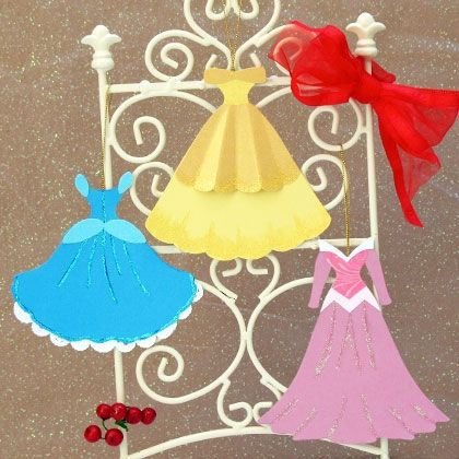 Decorated with sparkly glitter glue and paper doily ruffles, these paper gowns — modeled after the ones worn by Cinderella, Aurora, and Belle — are designed to dress up a tree or wreath.