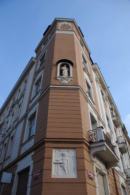 """""""Squadra e compasso, simboli massonici""""  In un angolo della casa neo-rinascimentale all'angolo tra la Kopernikova e Šmílovského, costruita nel 1907, c'è un bassorilievo che rappresenta un ragazzino nudo, che con la mano destra tiene un compasso su un tavolo da disegno e con la sinistra un righello a T. Sopra, un cartiglio contiene un compasso e una squadra che s'intersecano in modo da comporre una stella di David, simbolo dell'esagramma e quindi segno massonico per eccellenza."""