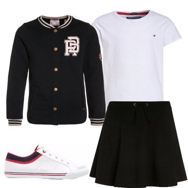 Outfit da ragazzina composto da felpa con bottoni in stile collegiale, t-shirt bianca, gonna ampia nera e sneakers basse bianche con particolari neri e rossi.