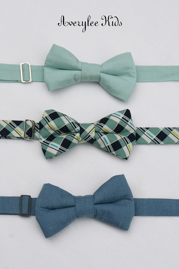 Bow ties are always a classic and todays color trend is strong for these current shades of dusty shale, dusty blue and navy blue. We offer this set in a solid dusty shale, navy blue and sage green plaid (SOLD OUT) or a dusty blue. We now offer two styles of bow ties, the classic look and our newest design that we call the diamond. Any of these bow ties will be the perfect accessory for your childs next special event: wedding, recital, holiday event or cake smash photo! (ky) Our adjustable…