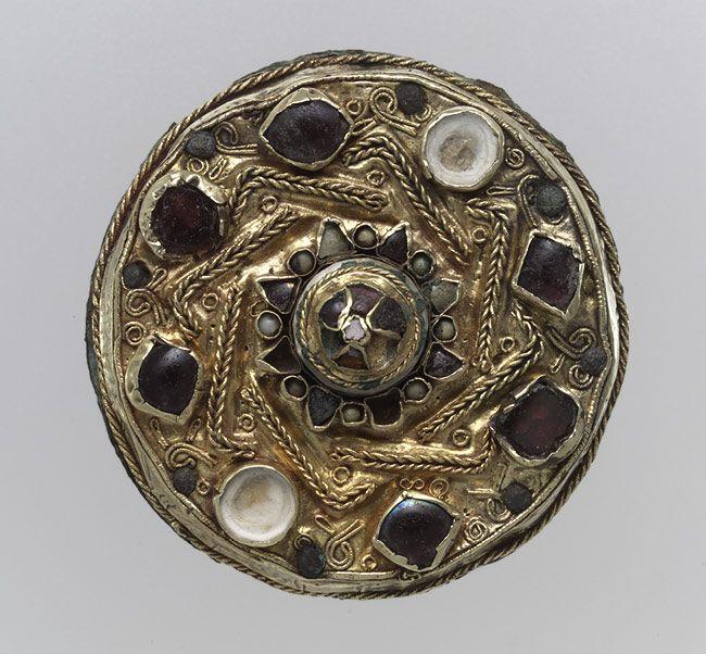 Frankish Disk Brooch, Gold sheet with filigree and inlays of garnet, glass, and mother-of-pearl, c. 675 - 700. Found in Niederbreisig, Germany- THIERRY III. 1) BIOGRAPHIE, 1: Né vers 657, le dernier fils de Clovis II et de la reine Bathilde, il succède à son frère Clotaire III en 673. Son maire du palais, le bouillonnant EBROIN, ne fait pas l'unanimité chez les Francs, et un conflit éclate entre les 2 hommes. Thierry et Ebroïn son tonsurés et envoyés dans des monastères.