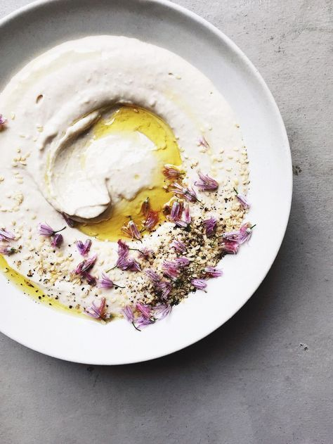 Tahini scattered with garlic flowers and toasted z'atar spice
