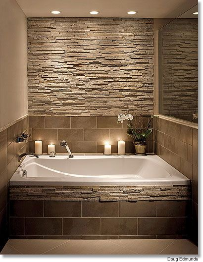 Bathroom stone wall and tile around the tub.