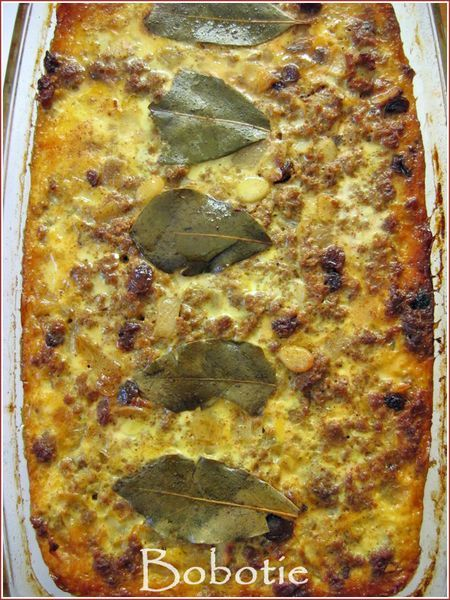 Bobotie is a classic South African dish of  gently-spiced ground meat full of raisins which is then oven-baked with a layer of savory egg custard on top to form a crust and keep the meat moist. Tradionally it is served with Yellow Rice. ♥ Cook Sisters!