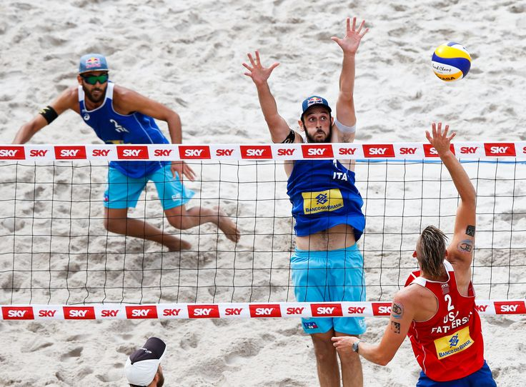 American Casey Patterson (right) hits against Paolo Nicolai (center) as Italian partner Daniele Lupo follows the action at the Rio Open net. #MensBeachVolleyball #BeachVolleyball #Block #USA
