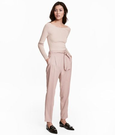 Powder pink. Pants in Tencel® lyocell with a tie belt, pleats at front, and a high waist. Side pockets, mock back pocket, and concealed side zip. Tapered