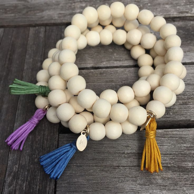 WHITE WOOD TASSEL MALA BRACELET These white wooden beads are calming and soothing to the touch. Choose from four colours of our special handmade tassels; yellow (sun), green (earth), blue (water), pink/purple (love & magic)  http://www.karmaladesigns.bigcartel.com/
