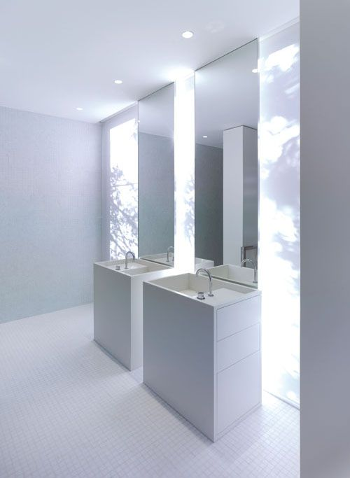 All white bathroom - Corian joinery combined with white mosaic tiles on the floors and walls.