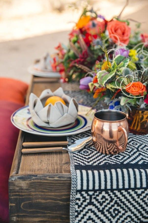 Outdoor wedding table decor idea: wooden tables set with a patterned table runner, bright florals and copper mules.