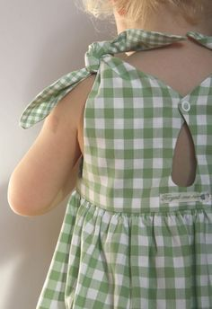 A little girl is wearing a green gingham dress with shoulder ties.