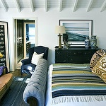 Eclectic bedroom with blue velvet tufted sleigh bed, black vintage dresser,