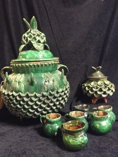 HILARIO ALEJOS MADRIGAL GREEN GLAZE PINEAPPLE PONCHERA PINEAPPLE SET CONSISTING OF 20 INCH COVERED PUNCH BOWL, A SET OF 6 CUPS WHICH HANG FROM THE PROTRUSIONS ON THE PUNCH BOWL AND A FOOTED PINEAPPLE SUGAR OR CANISTER BOWL, WITH LID. THIS HIGHLY COLLECTIBLE POTTERY FROM MICHOACAN, MEXICO IS IN GOOD CONDITION BUT NOT WITHOUT FLAWS. IT HAS A FEW ROUGH SPOTS HERE AND THERE AND THE TIP OF ONE CUP HOLDER NEEDS TO BE REPAIRED.